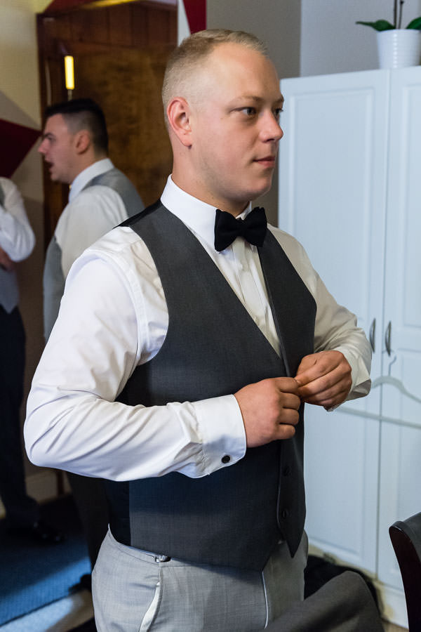 groom getting ready buttoning vest before wedding in new york city