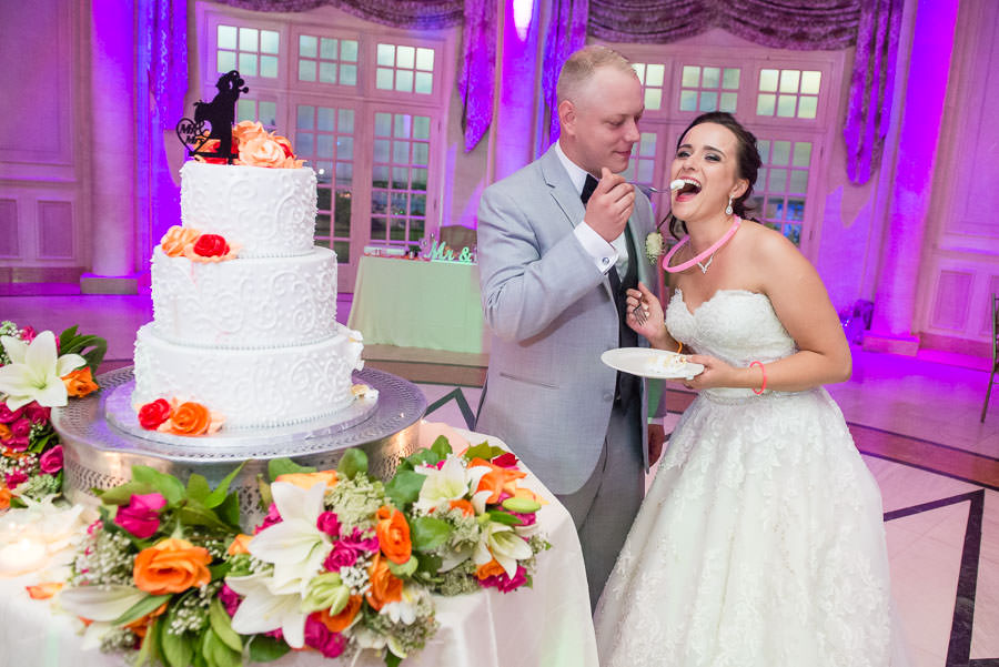 bride and groom eat wedding cake in terrace on the park