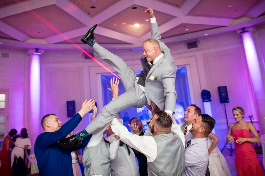 groomsmen throw groom in the air for funny photo in terrace on the park