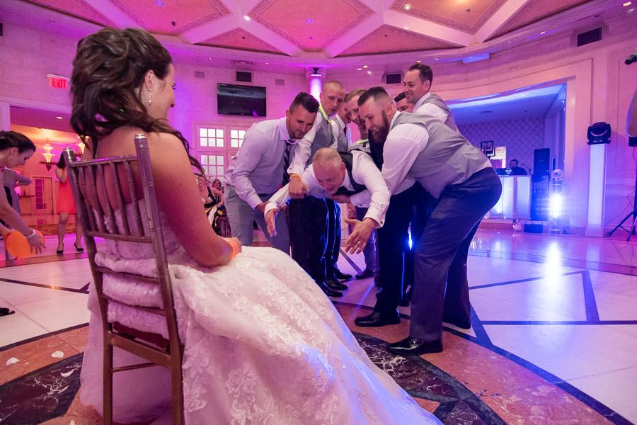 hilarious photo of groom getting garter off of bride's leg