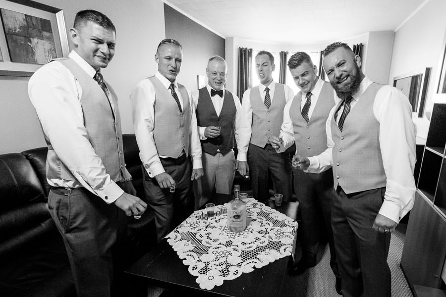 groom and groomsmen funny photo after taking shots before wedding funny faces