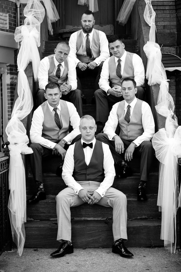 groom and groomsmen pose sitting serious