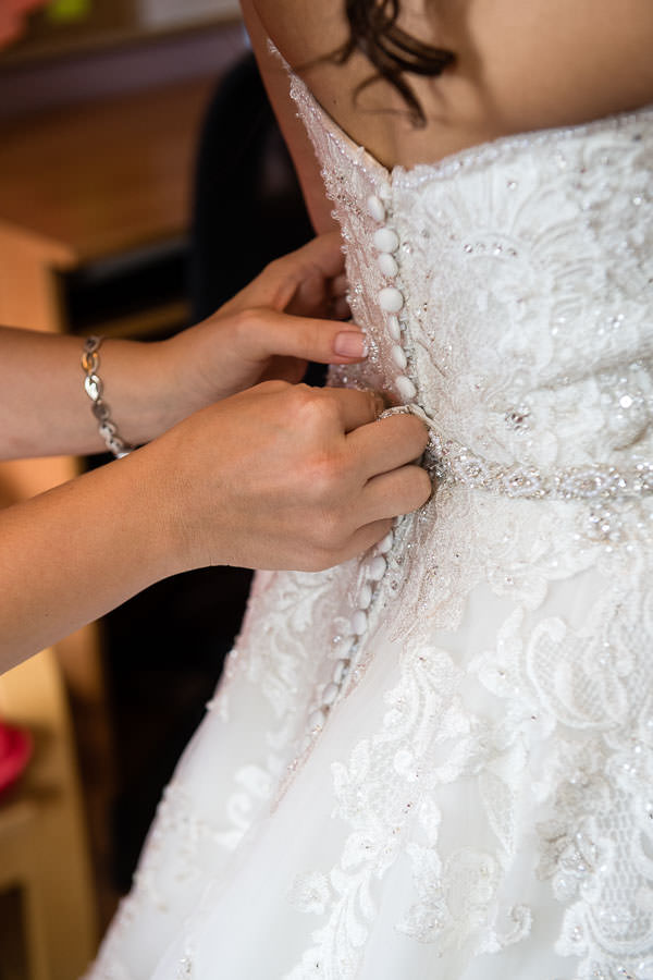 maid of honor helping bride buttoning wedding dress