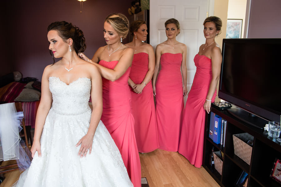 bride with all bridesmaids getting ready before wedding ceremony