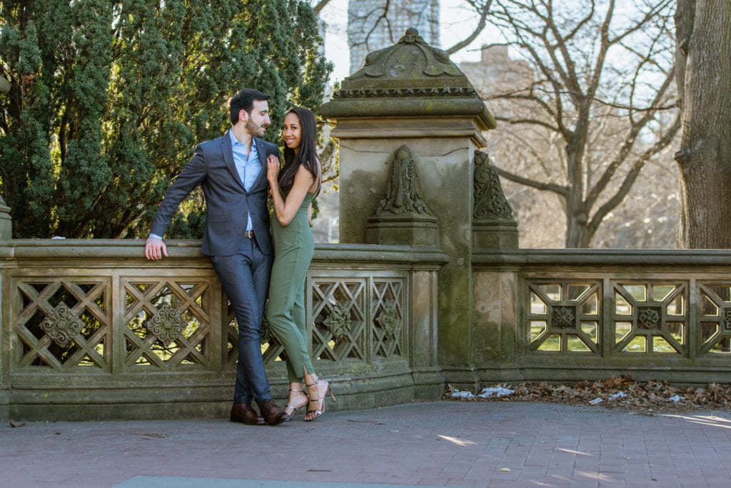 engagement couple in central park girl in green romper guy in suit by bethesda terrace