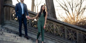 engagement couple in central park girl in green romper guy in suit by bethesda terrace walking down the steps