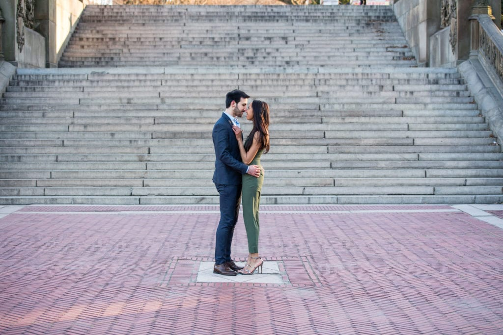 engagement couple in central park girl in green romper guy in suit by bethesda terrace with steps as background