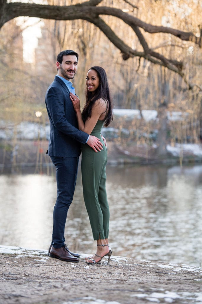 engagement couple in central park standing on rock with lake behind them