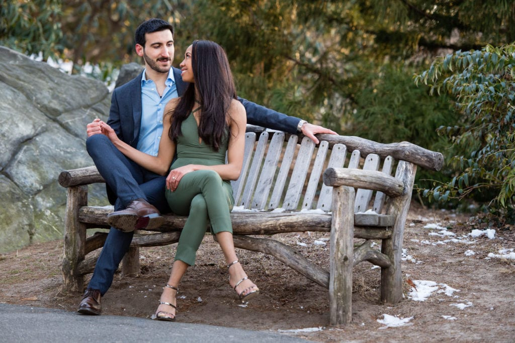 engagement couple in central park sitting on bench