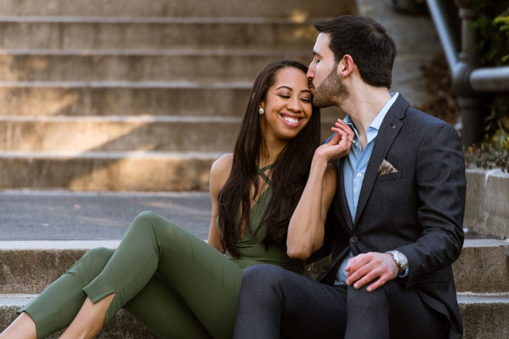 engagement couple in central park sitting on steps girl in green romper guy in suit