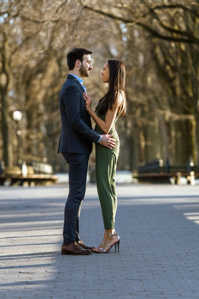 engagement couple in central park girl in green romper guy in suit standing with symmetrical trees by the mall in the fall