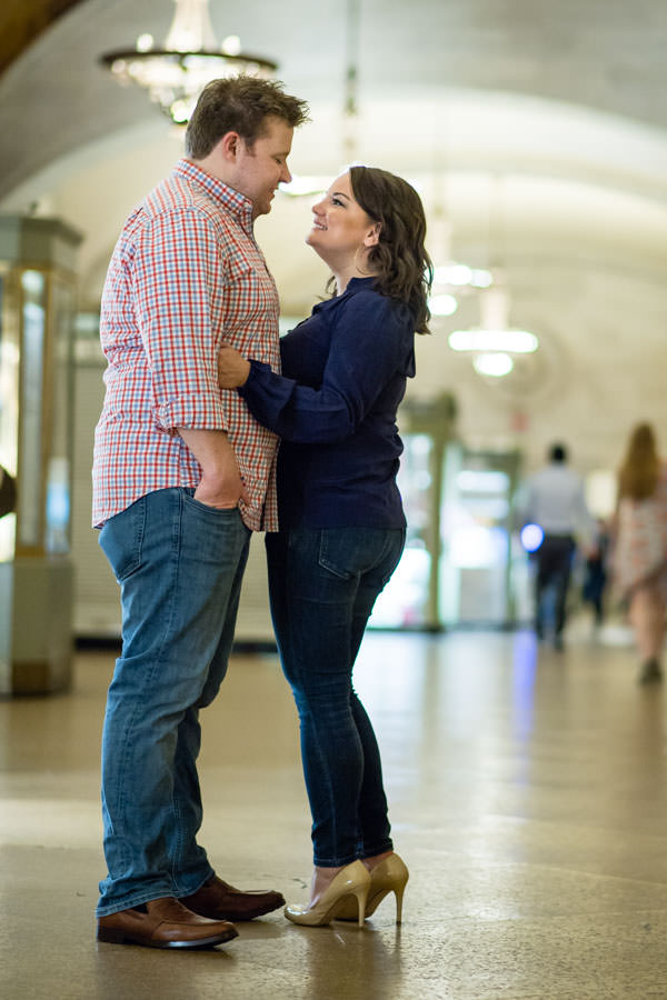 engaged couple standing under chandelier in grand central station during their engagement photo session