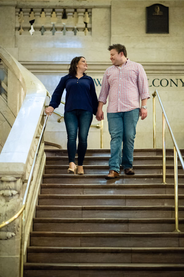 couple engagement session in grand central station in new york city with guy and girl going down the steps holding hands