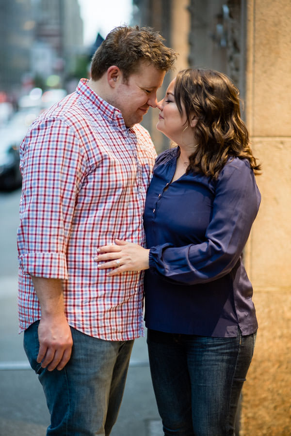 engaged couple holding each other outside of grand central station during engagement session