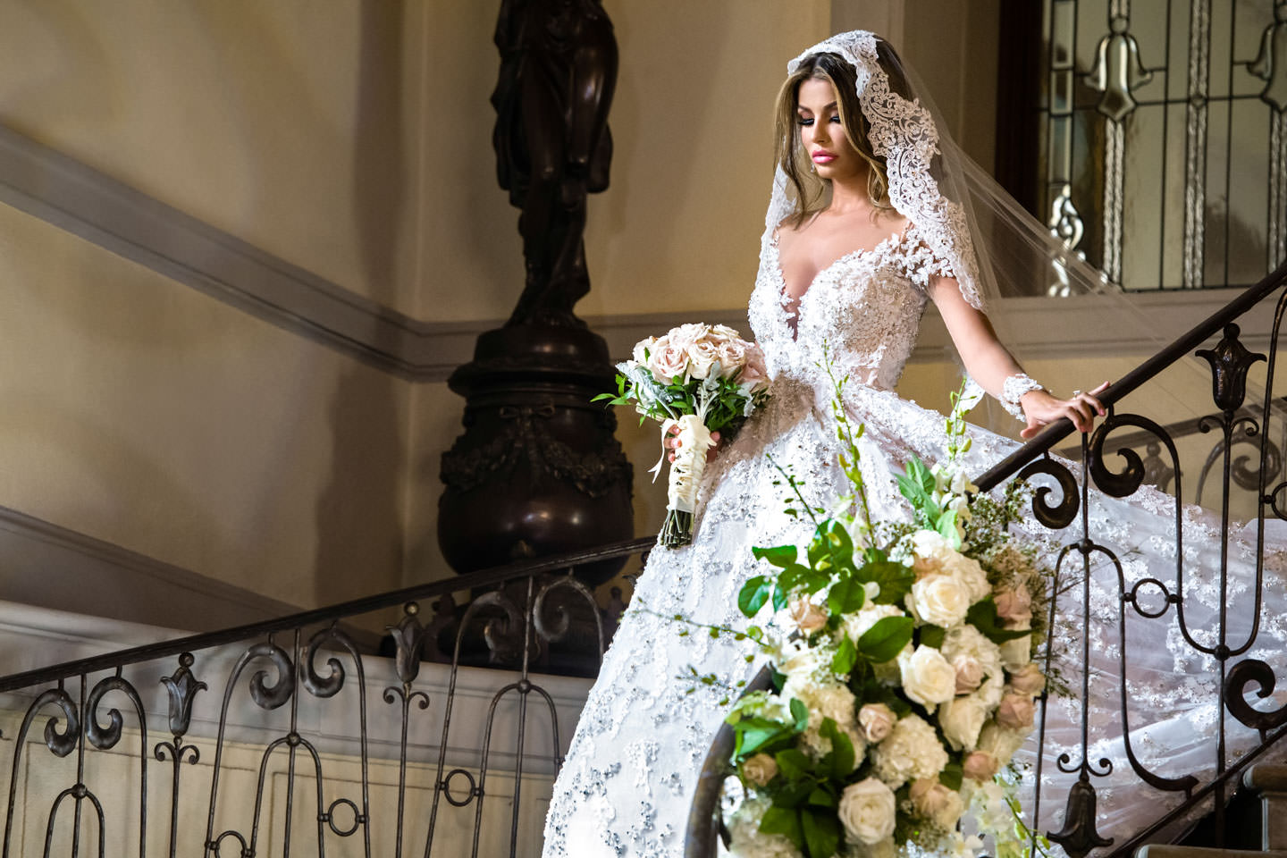 bride coming down steps in oheka castle in bridal reflections dress and jimmy choo shoes