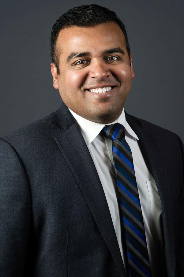 professional studio headshot indian man grey background