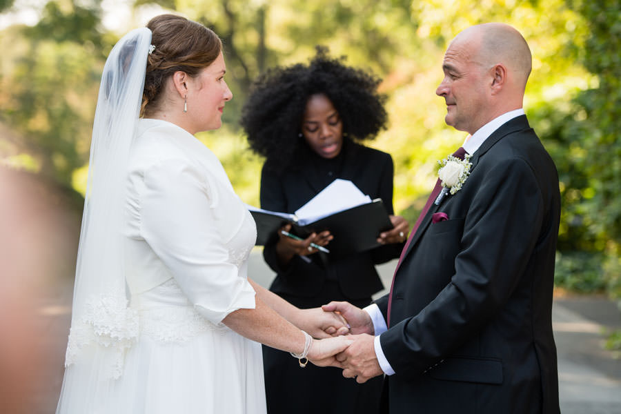 bride and groom happy with officiant at wedding ceremony in brooklyn botanic garden in nyc