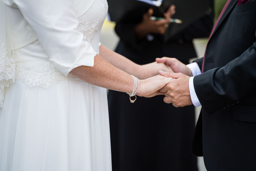 bride and groom holding hands at wedding ceremony in brooklyn botanic garden in nyc