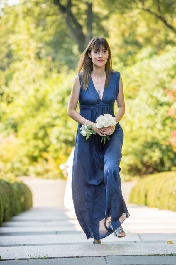 bridesmaid walking down aisle during procession at wedding in brooklyn botanic garden in nyc