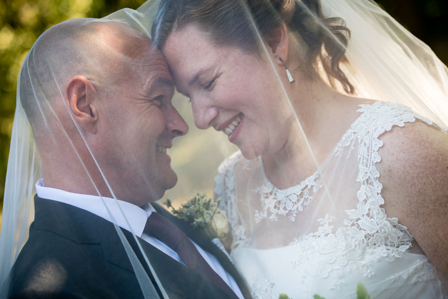bride and groom under wedding veil in brooklyn botanical gardens in nyc