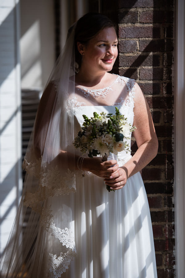 bride photo session next to window at picnic house in prospect park during wedding reception