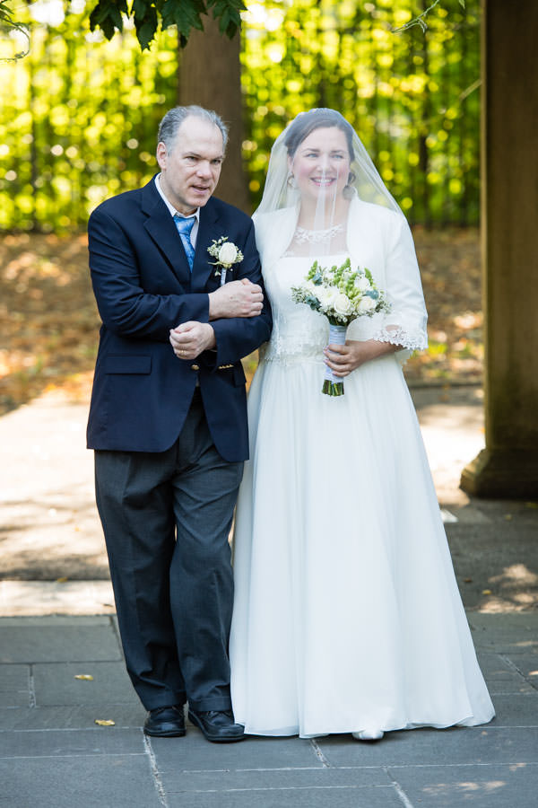bride walking with father at wedding in brooklyn botanic garden in nyc
