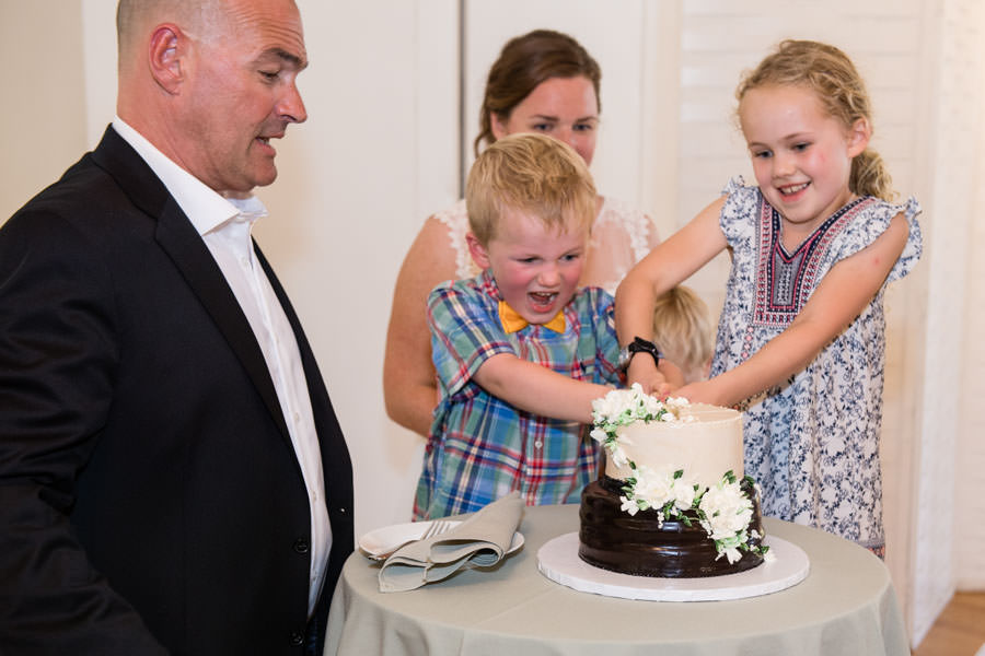 child helping bride and groom cutting cake at picnic house in prospect park
