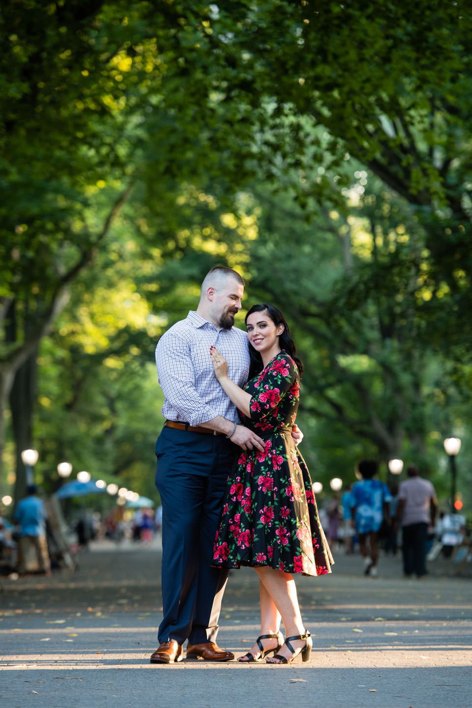 couple standing in front of the mall in central park nyc with girl wearing black and red flower dress