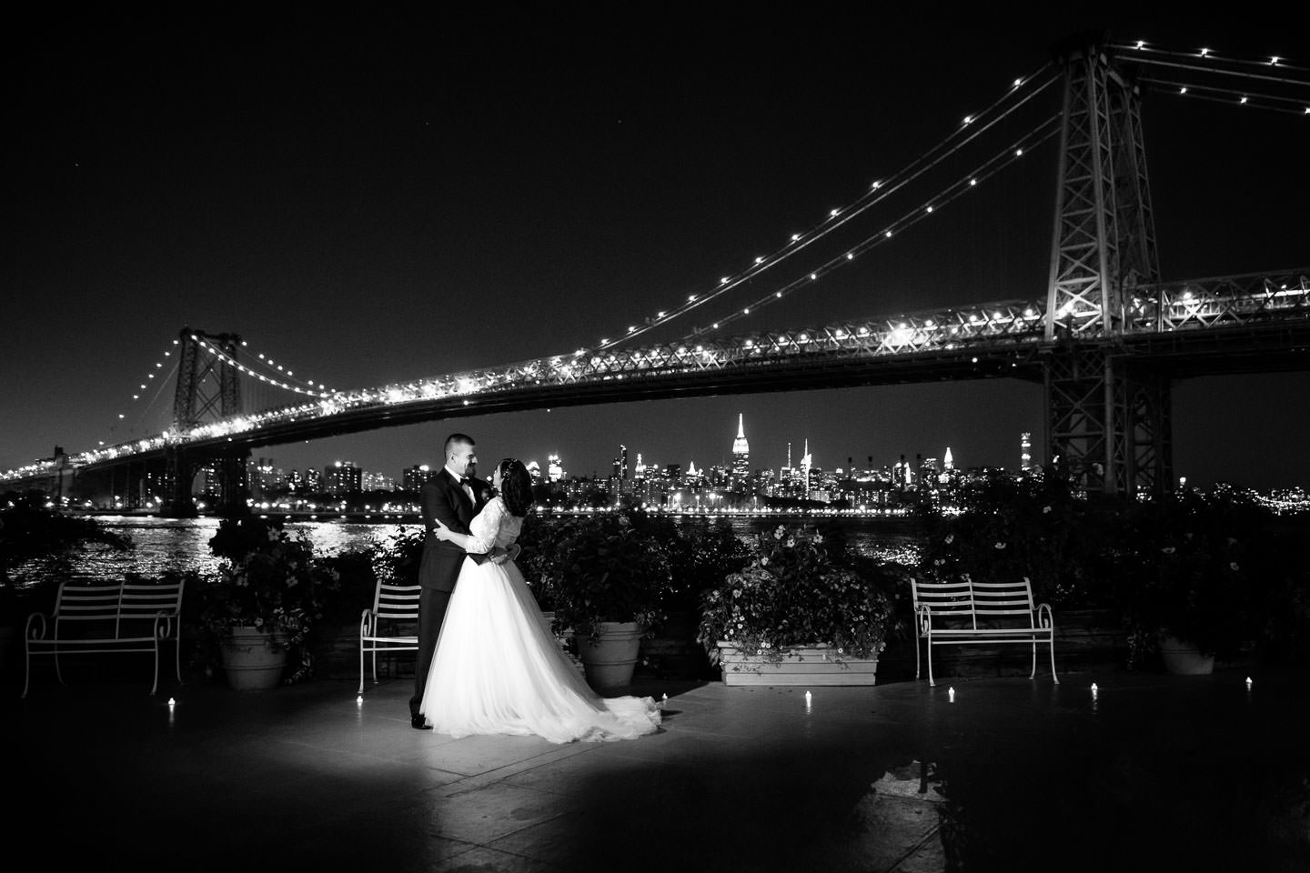 Bride and groom at night with NYC skyline in the background taken at wedding at Giando on the Water restaurant in Brooklyn