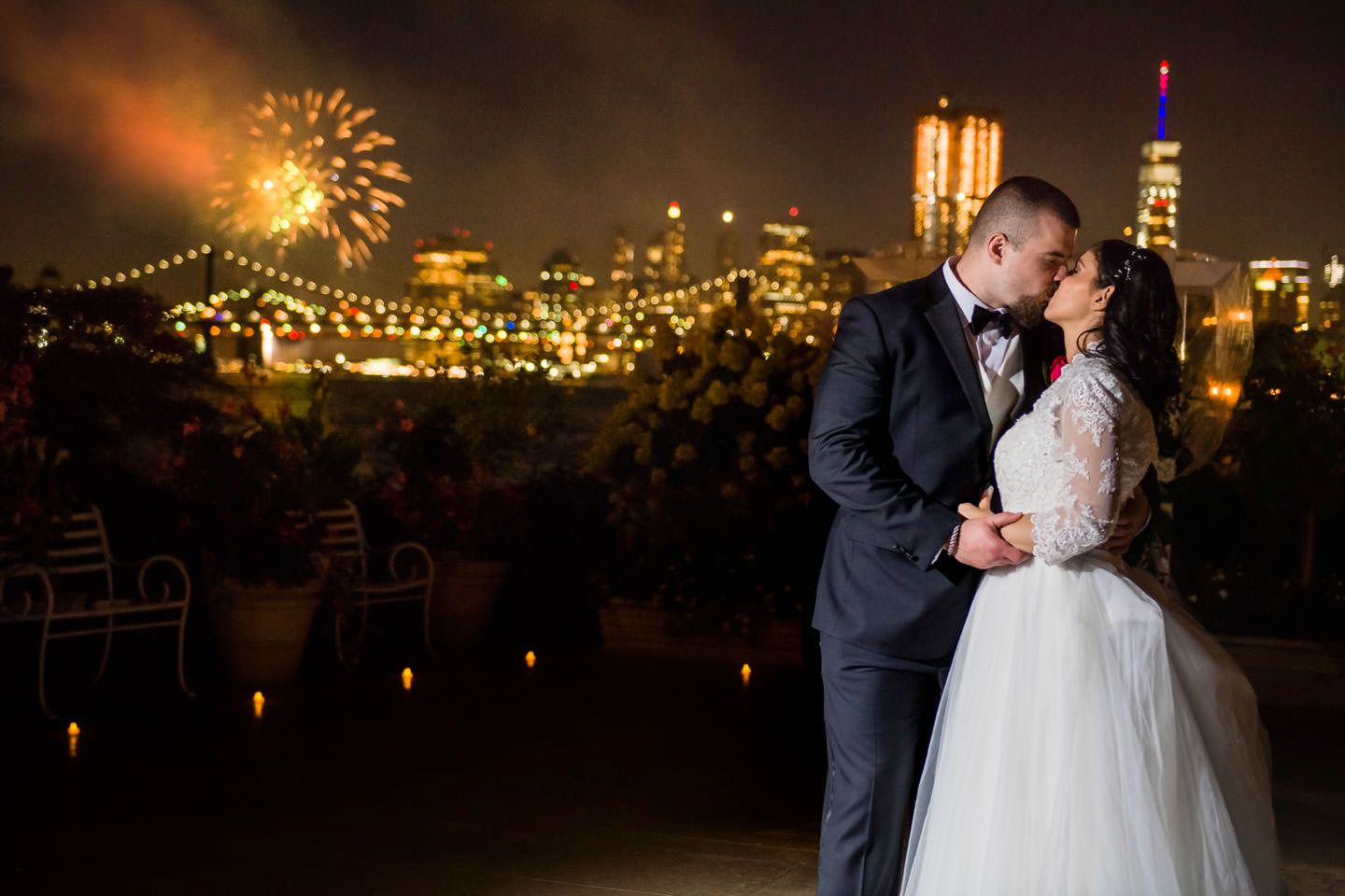 wedding couple kissing at night with NYC skyline and fireworks in the background taken at wedding at Giando on the Water restaurant in Brooklyn
