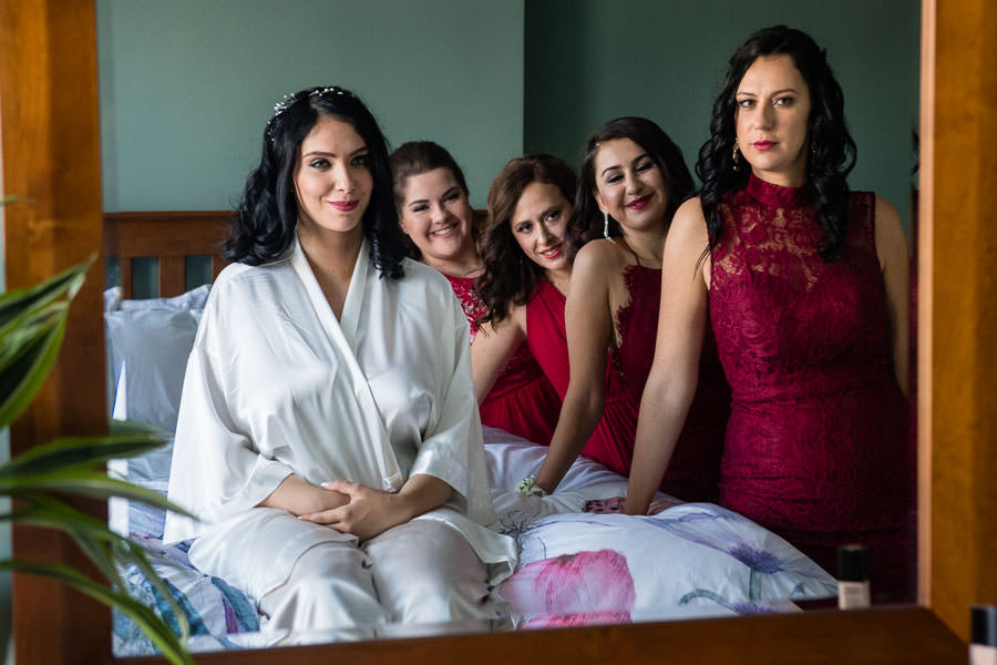 bride sitting on bed with bridesmaids looking at her in mirror