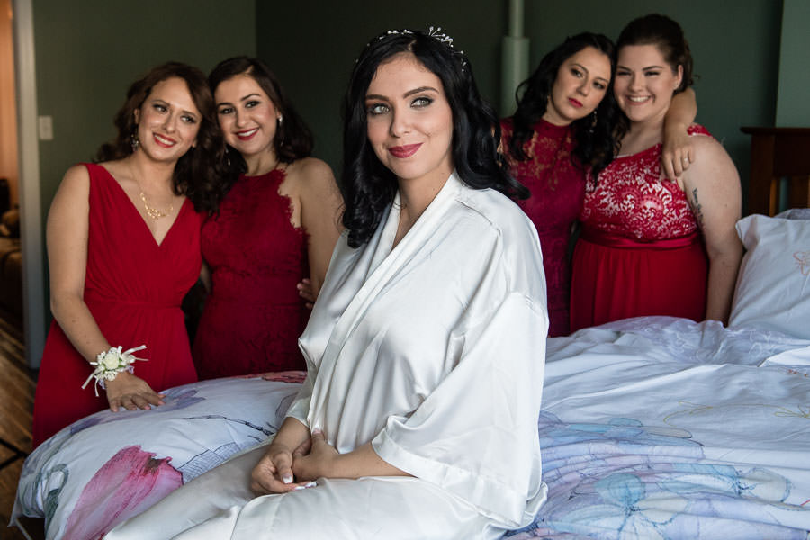 bride sitting on bed with bridesmaids behind her in maroon bridesmaid dresses