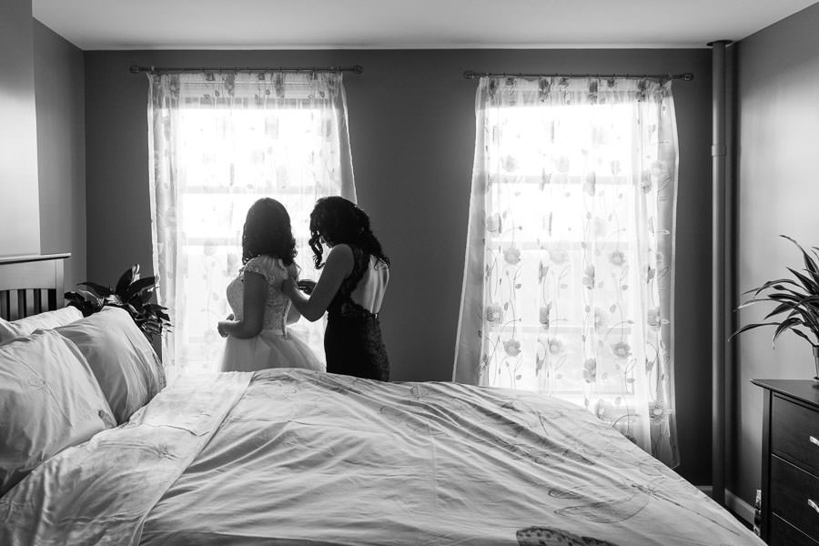 maid of honor helping bride put on her allure bridals wedding dress in front of window