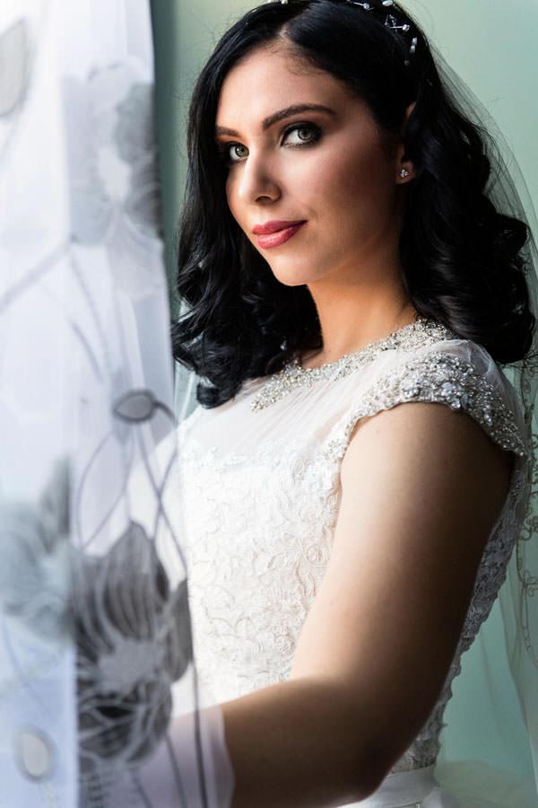 Bridal portrait by window in brooklyn ny wearing wedding dress by Allure Bridals