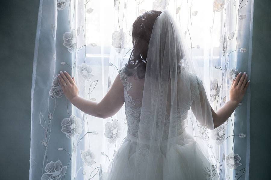 bride wearing Allure Bridals wedding dress looking out the window with smoke from atmosphere aerosol