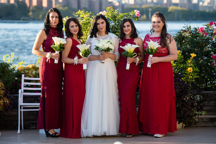 bride with bridesmaids in red bridesmaid dresses at wedding at Giando on the water in Brooklyn, NY