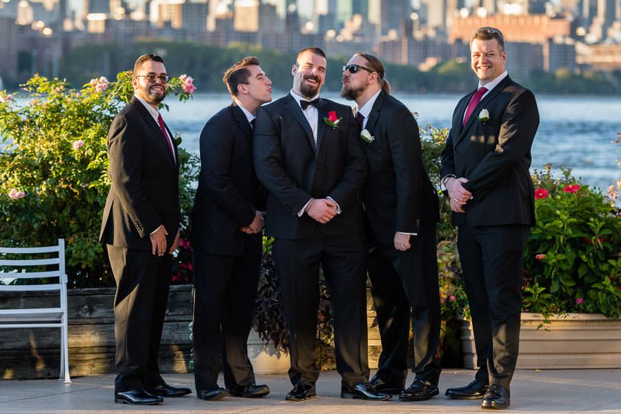 groomsmen funny photo kissing groom on cheek at wedding at Giando on the water in Brooklyn, NY