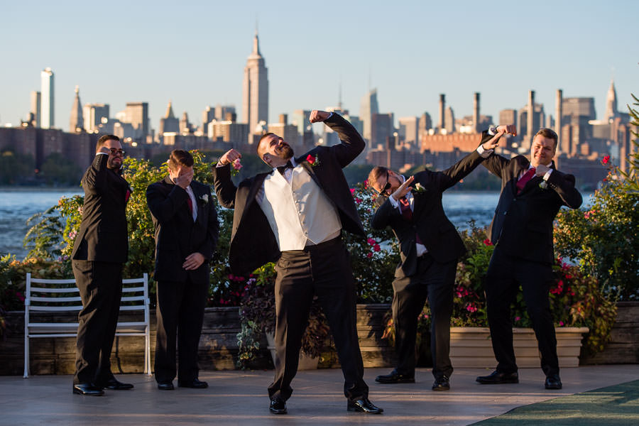 groom flexing muscles for funny wedding photo at wedding at Giando on the water in Brooklyn, NY