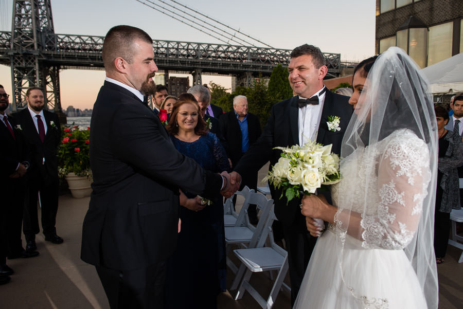 groom shaking bride's father's hand during procession at wedding at Giando on the water in Brooklyn, NY