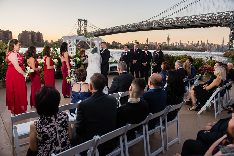 wedding ceremony outside at wedding at Giando on the water in Brooklyn, NY with Williamsburg bridge in the background