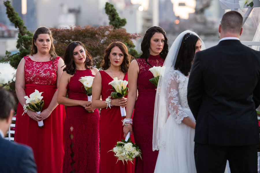bridesmaids in red dresses at wedding ceremony at Giando on the water in Brooklyn, NY