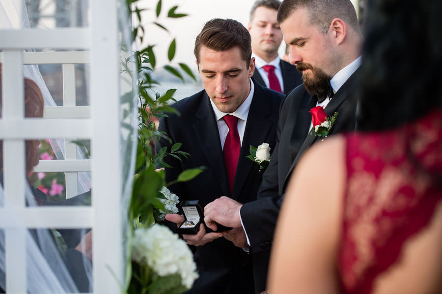best man giving rings to groom at wedding at Giando on the water in Brooklyn, NY