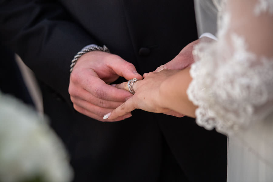 groom putting wedding band from Sawa Jewlery on bride's finger