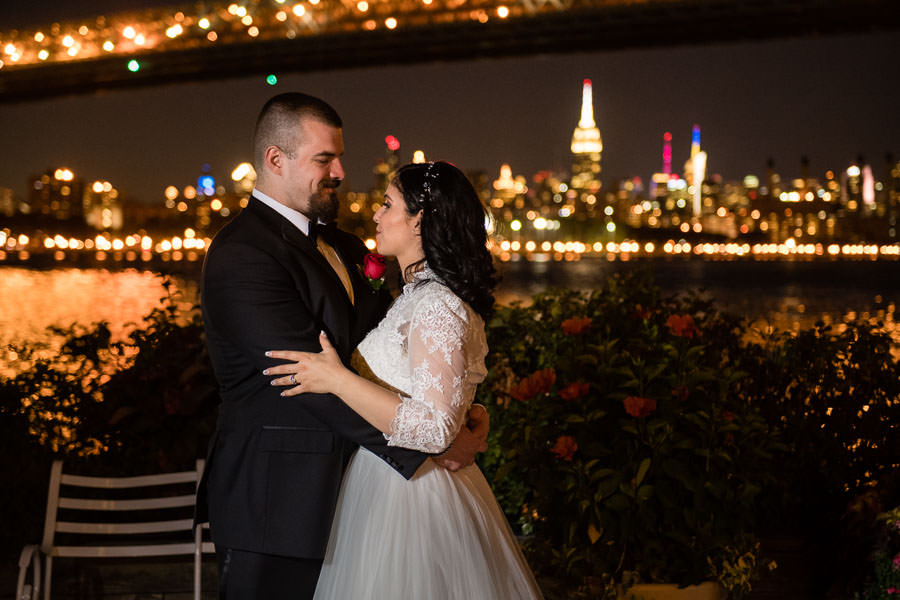 bride and groom at night with williamsburg bridge and NYC skyline  at wedding at Giando on the water in Brooklyn, NY