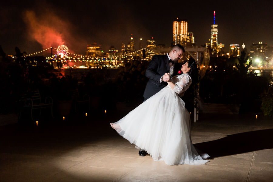 bride and groom at night with williamsburg bridge and NYC skyline  at wedding at Giando on the water in Brooklyn, NY with fireworks in the background