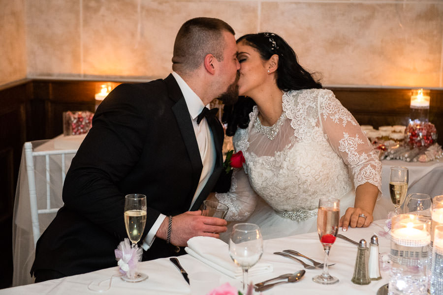 wedding couple kissing at their table during reception at giando on the water