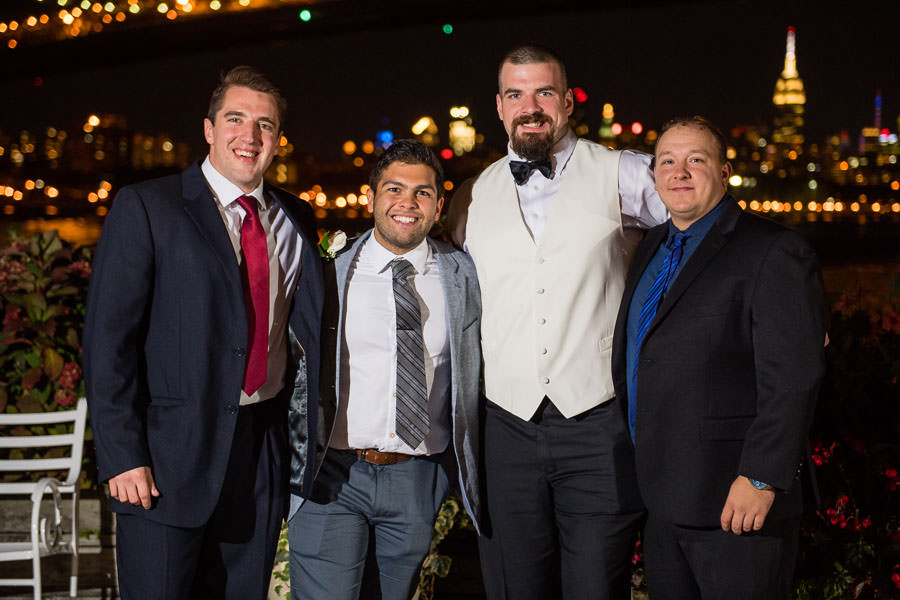 groom and friends at giando on the water with nyc skyline at night