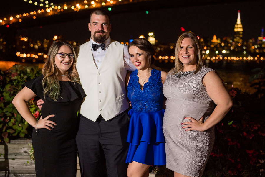 groom with guests in front of nyc skyline at night at giando on the water nyc wedding venue