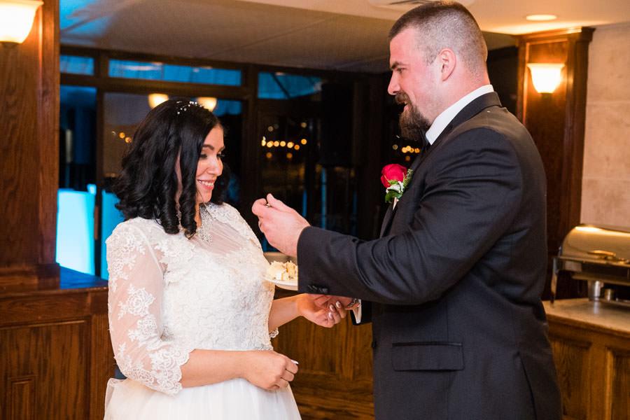 groom feeding cake to bride at their wedding