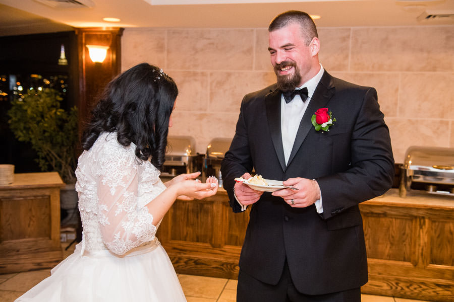 bride and groom feed each other cake at their wedding in brooklyn ny